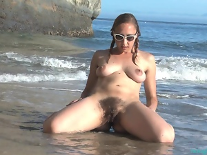 Hairy babe plays in the sand