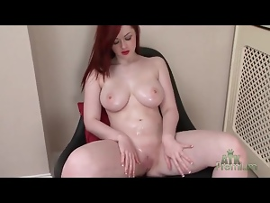 Curvy redheaded girl rubs oil into her body