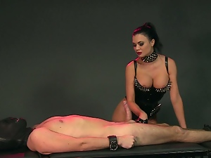 Brunette mistress in latex tortures her slave.