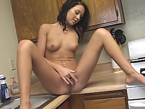 Sexy brunette masturbates in the kitchen and gets facialized