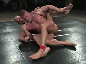 Oiled up guys fight on the mat and have wild anal sex