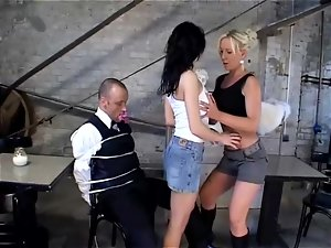 Two sexy babes play with each other's pussies in front of a bound guy