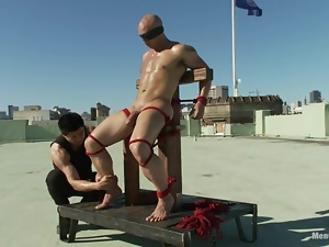 Bald John Magnum gets tied up and tortured by a man