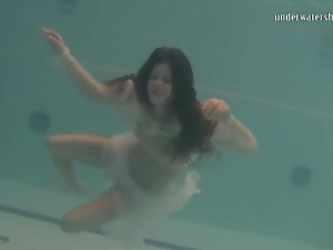 Young brunette swims in sheer white clothes