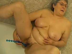 Fat four eyed granny with saggy udders masturbates with beads in bathtub