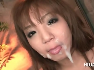 Asian slut blowing two cocks gets a messy facial