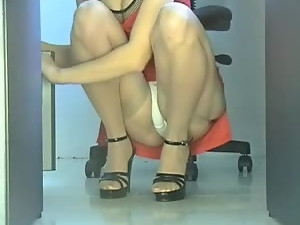Girl in red dress sits in toilet cabin and shows her sexy legs