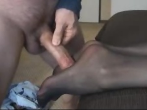 Pretty girl gives a footjob and gets cum on her nylon pantyhose