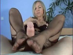 Mature blonde gives a footjob to her horny man indoors