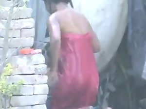 neighbour young lady bathing outside in village