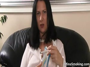 Sexual dark haired chick smokes a cigarette