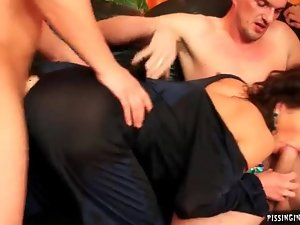 Urine soaked clothed slut takes a gangbang