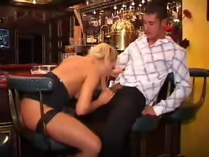 Chick in a gorgeous cocktail dress sucks cock in bar