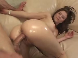 Her oiled up ass shines as he pounds her pussy