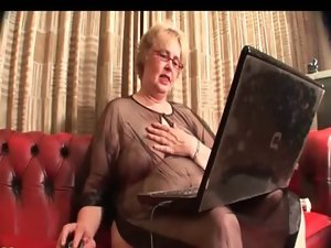 Attractive mature tramp in boots pleasuring her cunt on the couch