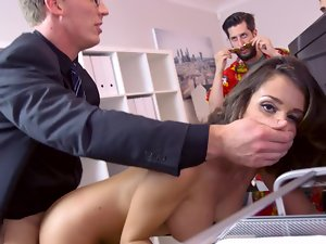 A dark haired with large knockers is getting penetrated in the office