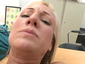 A blond is on the table, nude and pushing a rubber toy into her twat