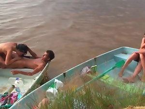 Sensual people are having group sex on the beach in a tiny boat
