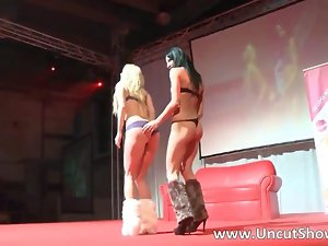 Two lewd ladies get on stage to finger film