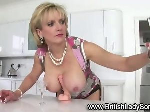 Solid artificial blond english nympho rides a Rubber toy on a counter top