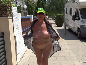 Attractive mature ambling down the street flashing charms